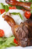 Roasted duck leg with rice and basil on lettuce vertical Stock Photography