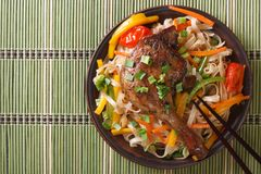Roasted duck leg with rice noodles on a bamboo table  top view Stock Photos