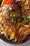 Roasted duck leg with rice noodles and vegetables macro Royalty Free Stock Photo