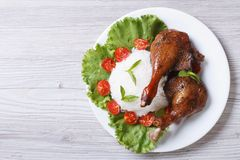 Roasted duck leg with rice and vegetables top view of a horizont Stock Photos