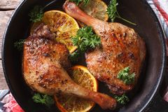 Roasted duck legs in a pan with oranges top view horizontal. Roasted duck leg with oranges in a pan close-up. horizontal view from above Royalty Free Stock Images