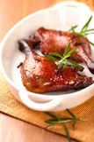 Roasted duck legs with rosemary sprigs Stock Photos