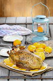 Roasted duck with oranges on wooden table Stock Photo