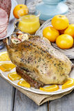 Roasted duck with oranges on wooden table Stock Images