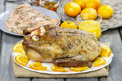 Roasted duck with oranges on wooden table Royalty Free Stock Photo