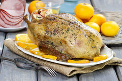 Roasted duck with oranges on wooden table Royalty Free Stock Image