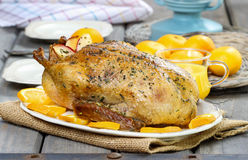 Roasted duck with oranges on wooden table Stock Image