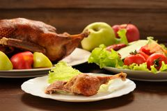 Roasted duck served with fresh vegetables and apples on wooden t Stock Photo