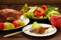 Roasted duck served with fresh vegetables and apples on wooden t Stock Images