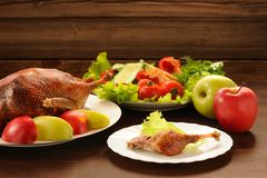 Roasted duck served with fresh vegetables and apples on wooden t Royalty Free Stock Image