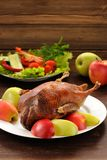 Roasted duck served with fresh vegetables and apples on wooden t Royalty Free Stock Images