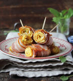 Roasted egg rolls with crispy bacon and spinach Stock Image
