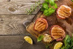 Roasted filet mignon with herbs and spices. Rustic wood background stock image