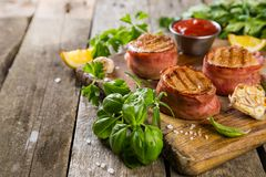 Roasted filet mignon with herbs and spices. Rustic wood background royalty free stock photography