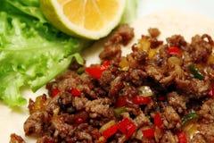 Roasted finhackade nötkött med chilipeppar på tortillan med grönsallat och citronen Arkivfoton