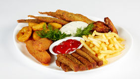 Roasted fish and chicken wings with french fries. Roasted fish and chicken wings served with french fries and rusks isolated on a white plate Royalty Free Stock Photo