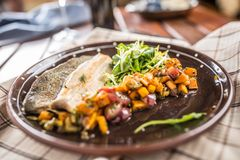 Roasted fish fillet with pumpkim pieces and herb decoration in p Royalty Free Stock Photography