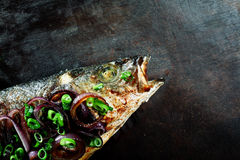 Roasted Fish Garnished with Red and Green Onions Royalty Free Stock Image