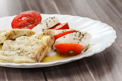 Roasted fish and Italian caprese salad Royalty Free Stock Photography