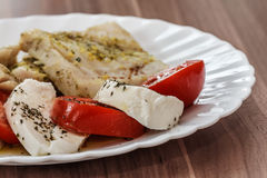 Roasted fish and Italian caprese salad Stock Images