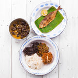 Roasted fish with lemon, snail, squid, beef, fried shallot, and white rice Royalty Free Stock Image