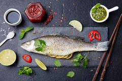 Roasted fish with sauces, fresh herbs and lime Stock Image