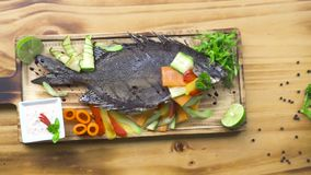 Roasted fish with vegetable garnish in bbq restaurant. Food composition grilled fish with vegetable and spices. Appetizing dishes in seafood restaurant. Food stock video