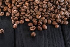 Roasted fragrant beans of black coffee are scattered on a black table stock photo