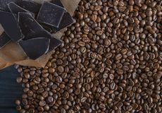 Roasted fragrant beans of black coffee are scattered on a black wooden table, on which black chocolate is lying royalty free stock photos