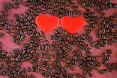 Roasted fragrant coffee beans and two hearts on a red felt background. Daylight stock photo