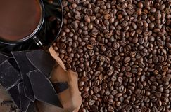 The roasted fragrant grains of black coffee are scattered on a black wooden table and there is a brown glass cup with stock photos