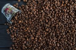Roasted fragrant grains of black coffee are scattered from a white metal bucket on a black table royalty free stock photo