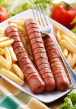 Roasted frankfurters with French fries Stock Photography