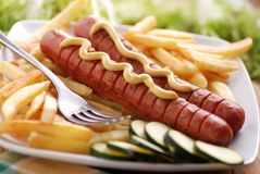 Roasted frankfurters seasoned with mustard. Served with French fries on dish Stock Photo