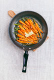 Roasted (fried) baby carrots on a baking pan Stock Image