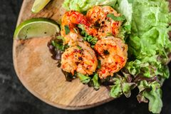 Roasted fried shrimps with green salad and lime on wood, top view. Black background stock image