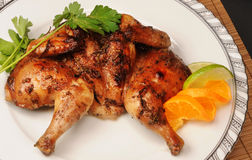 Roasted game. Roasted cornish game hen on a white plate Royalty Free Stock Photo