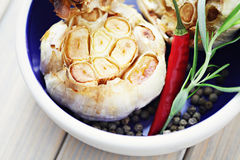 Roasted garlic. With chilli pepper and rosemary - herbs and spices royalty free stock photography