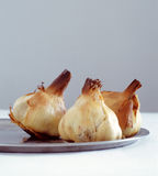 Roasted garlic on a metal plate Stock Photos