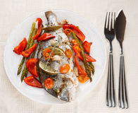 Roasted gilt-head bream with vegetables on plate. Roasted gilt-head bream with vegetables in plate on table royalty free stock photo