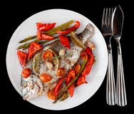 Roasted gilt-head bream with vegetables on plate, isolated on bl Royalty Free Stock Images