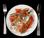 Roasted gilt-head bream with vegetables on plate, isolated on bl Royalty Free Stock Photo