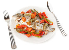 Roasted gilt-head bream with vegetables on plate, isolated on wh Stock Photography