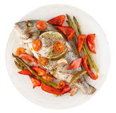 Roasted gilt-head bream with vegetables on plate, isolated on wh Royalty Free Stock Photography