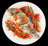 Roasted gilt-head bream with vegetables on plate, isolated on wh Royalty Free Stock Photo
