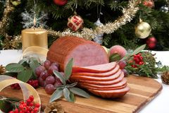 Roasted Glazed Christmas Ham. Roasted ham with fresh thyme for Christmas party. XMas tree in the background, surrounded by ornaments. Rustic style Royalty Free Stock Photography