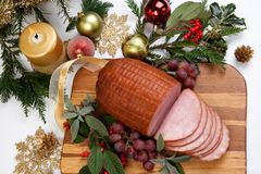 Roasted Glazed Christmas Ham. Roasted ham with fresh thyme for Christmas party. XMas tree in the background, surrounded by ornaments. Rustic style Stock Photos