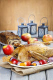 Roasted goose with apples and vegetables on wooden table. Stock Images