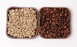 Roasted and green coffee beans in two ceramic saucers on white background Royalty Free Stock Photos