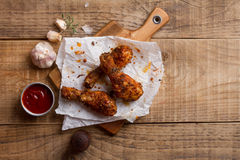 Roasted (griiled) chicken drumstick on cutting board Stock Image